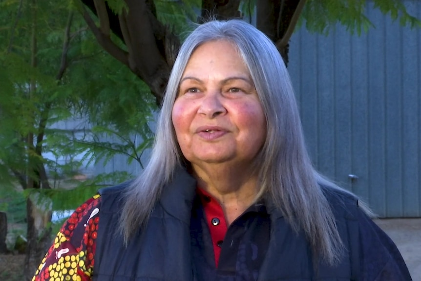 A woman with grey hair and Aboriginal artwork on her shirt.