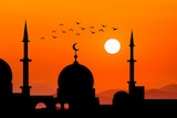 The sun sets behind a mosque.