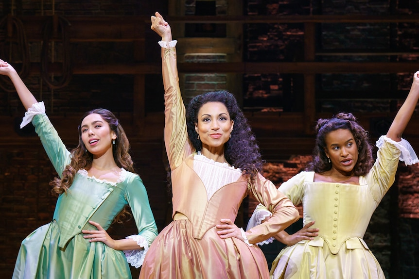 Stage shot showing three women in pastel-coloured 18th century gowns, each with one hand on hip and the other in the air.