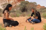 Two young women sit on red soil looking down. Behind them is a large rockface and expanding blue sky.