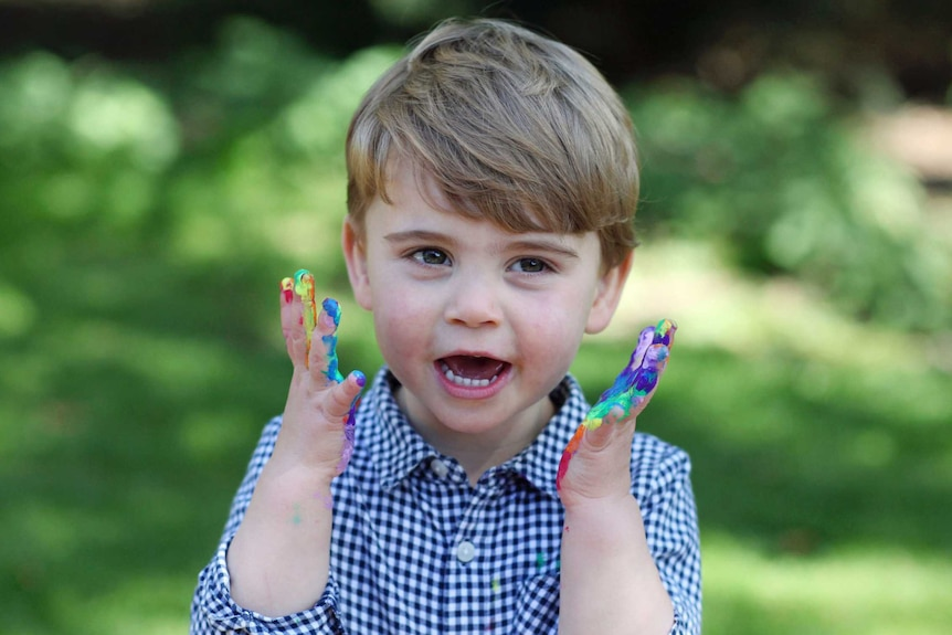 Prince Louis is pictured with a huge smile and with his hands covered in paint.