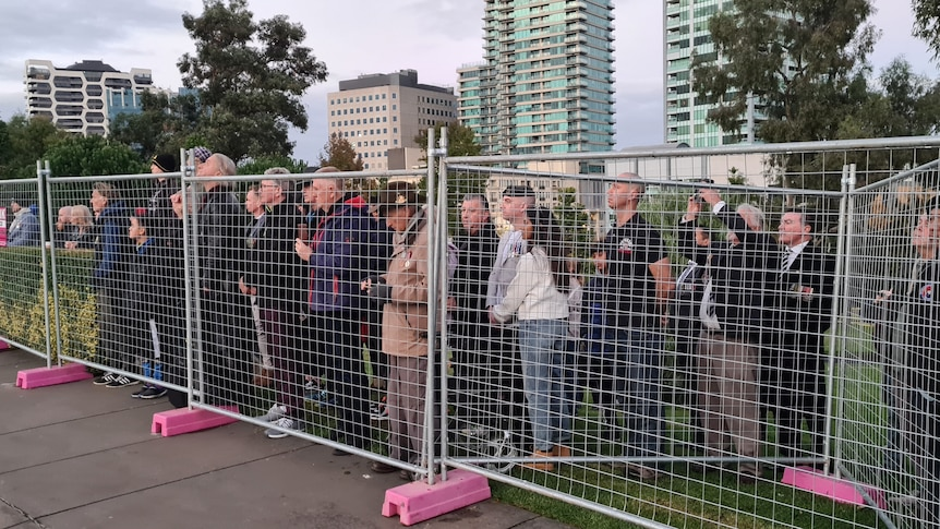 A crowd watches the Anzac Day dawn service from behind a temporary fence.