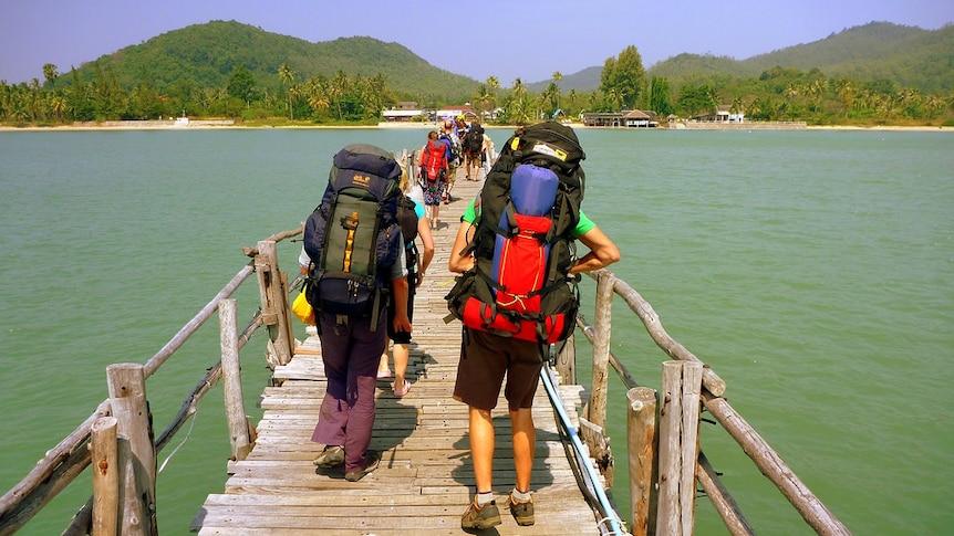 Backpackers walking over a bridge