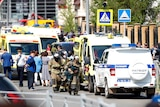 Firefighters walk past ambulances and police cars and a truck parked at a school after a shooting in Kazan, Russia.