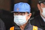 Carlos Ghosn wears a blue cap with an electric bolt on it and a mask as he leaves a detention centre.