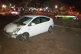 A badly damaged white car in dirt with a police on the road behind