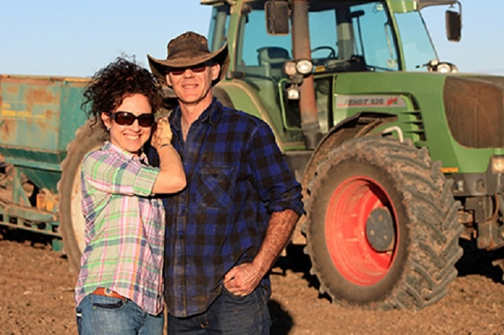A man and a woman standing in front of a tractor.