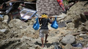 A man carries belongings from his toppled house in Balarola, Indonesia
