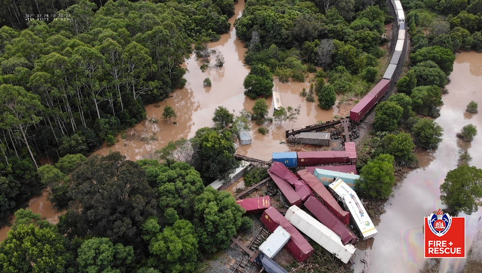 Aerial view of derailed goods train surrounded by flooded paddocks with carriages in water and on their side
