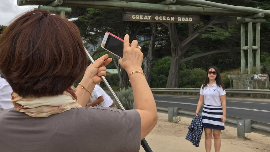 """A woman poses for a photo under a sign that says """"Great Ocean Road"""". In the foreground another woman takes her picture"""