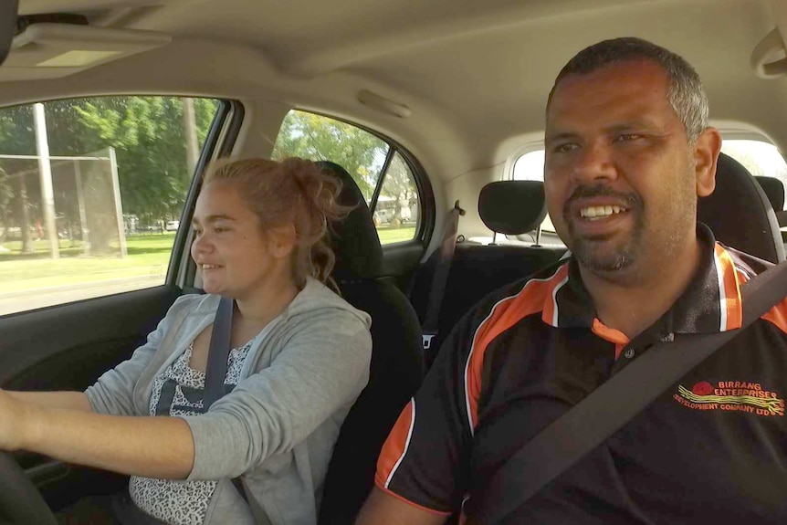 A driving instructor and a young girl sit in a car