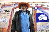 Colour photograph of artist Mumu Mike Williams standing in front of his artwork, painted onto old Australian Post mailbags