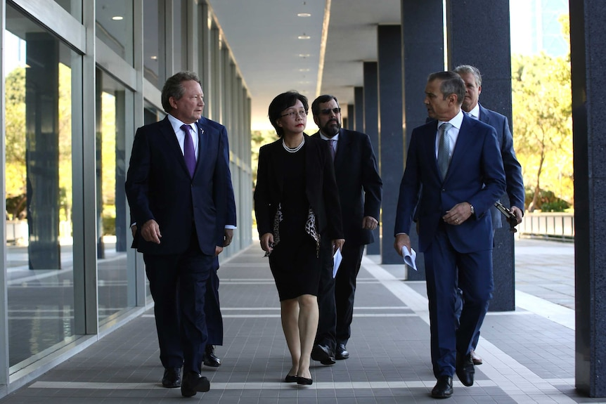 A group of business people and politicians dressed in corporate suits walk towards the camera outside a building.