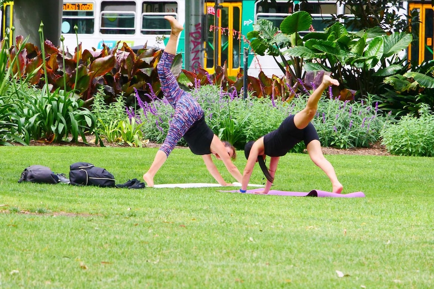 Two women do yoga in a park.