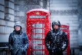 A man and a woman bundled up in winter gear walk through snow with red telephone boxes behind them
