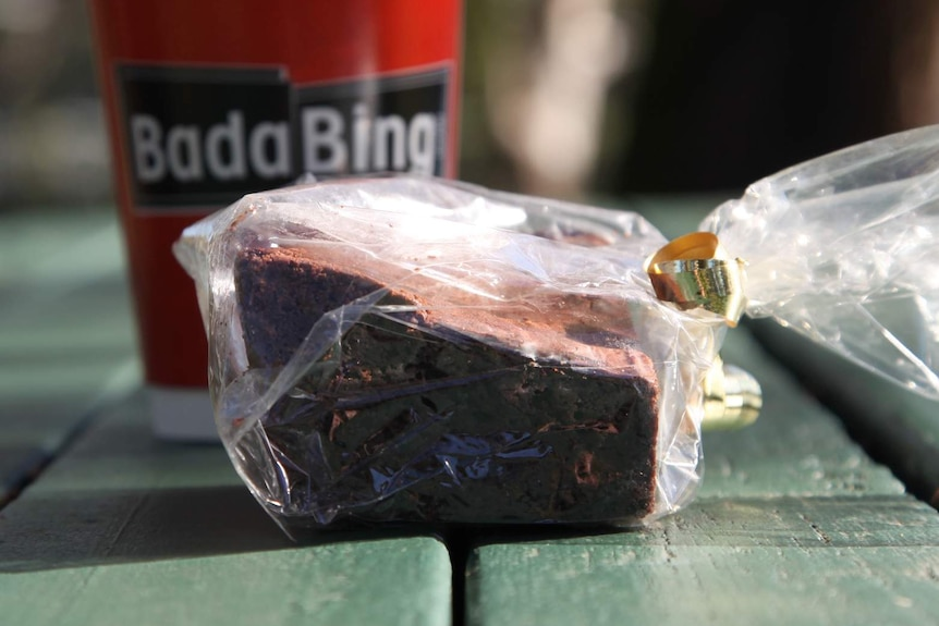 A chocolate brownie and takeaway coffee from Bada Bing, on a picnic table.