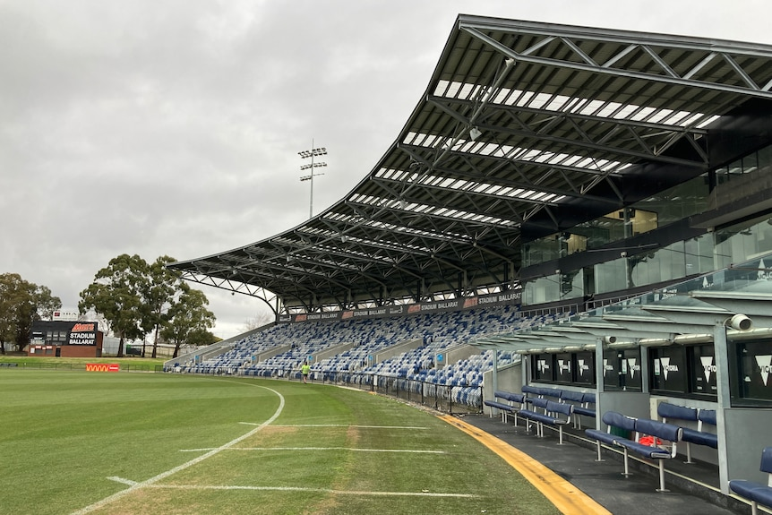 An empty grandstand next to a football oval on a cloudy day.
