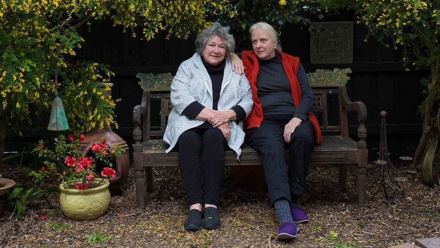 Hilary and Kristin sit on a bench surrounded by their colourful garden.