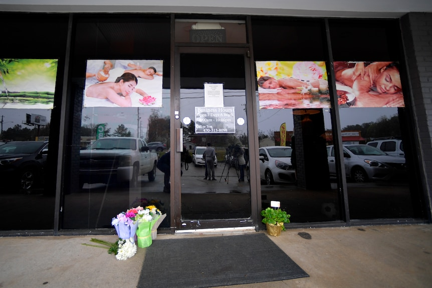 A make-shift memorial with flowers is seen outside a massage business.