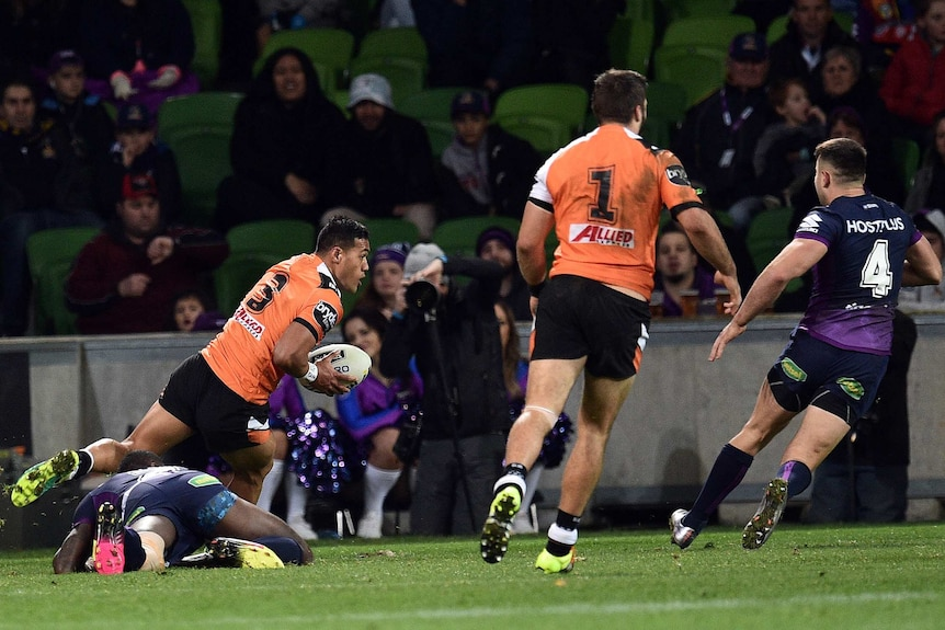 Tim Simona runs in to score a try for Wests Tigers