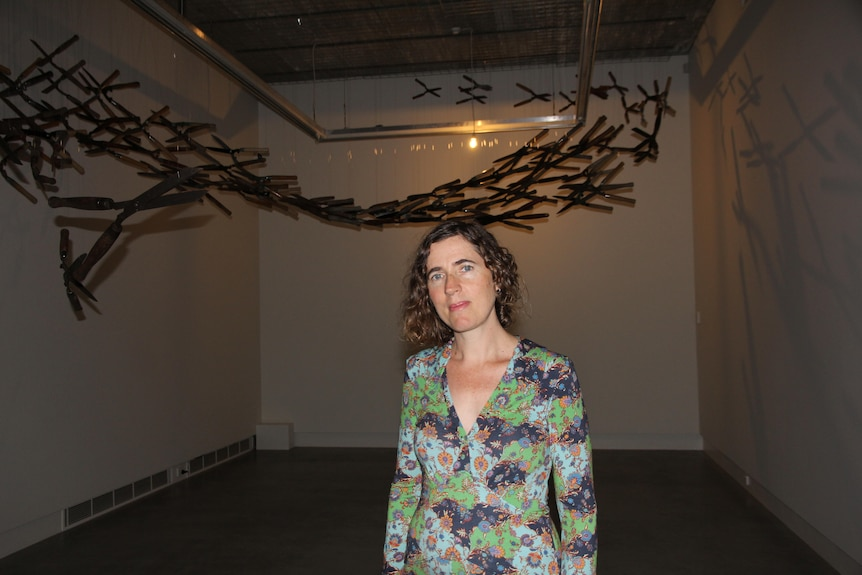 Tamara Dean stands inside a room wearing a floral dress with a wooden sculpture on the wall behind her.