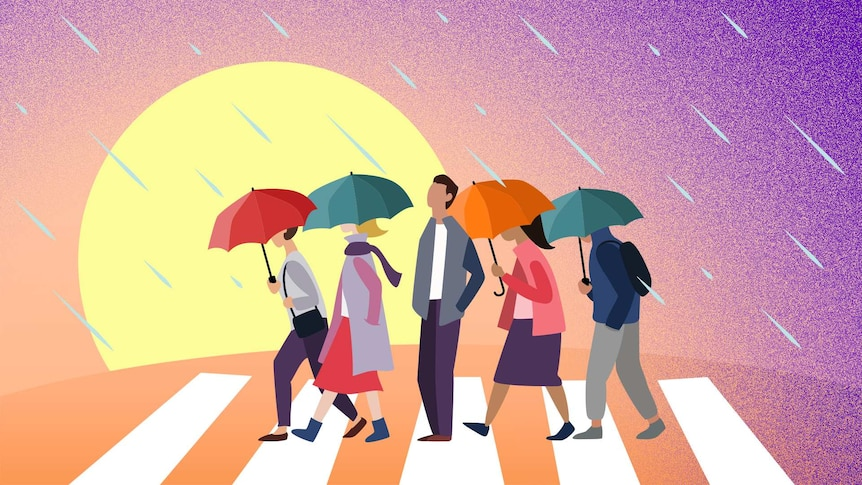 A man without an umbrella stands on a pedestrian crossing facing the rain while others with umbrellas pass him by.