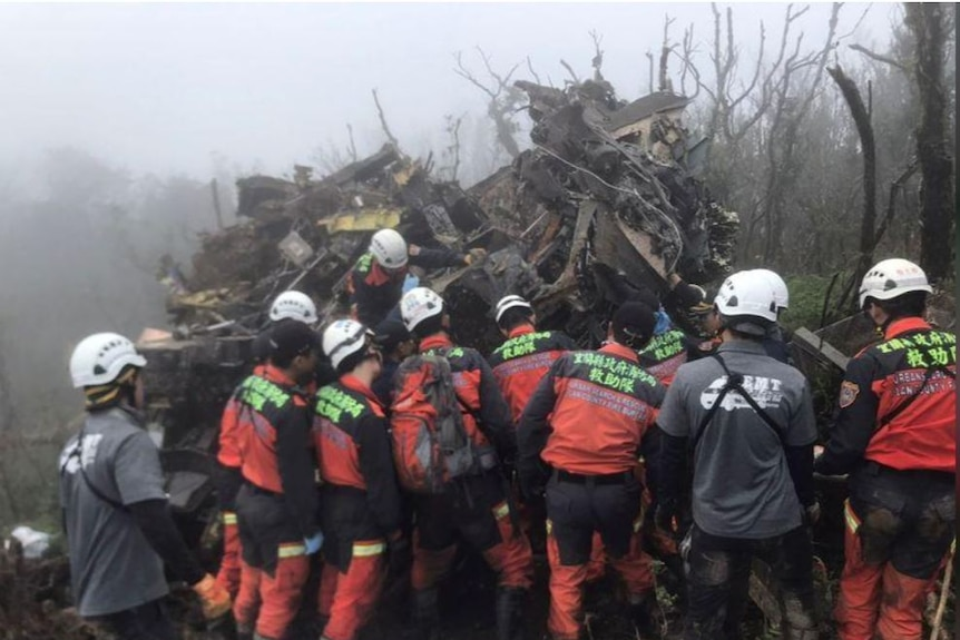A crowd of rescue workers look at the wreckage of a Black Hawk helicopter in foggy scrubland.