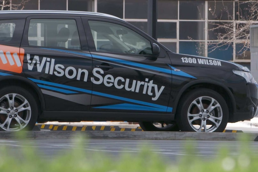 A black SUV with Wilson Security on its side parked in a carpark