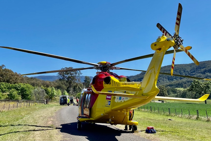 A yellow and red helicopter landed on a country road.
