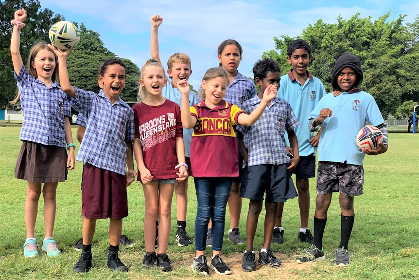 a group of primary school children cheering, dressed in Blue and Maroon cheering.