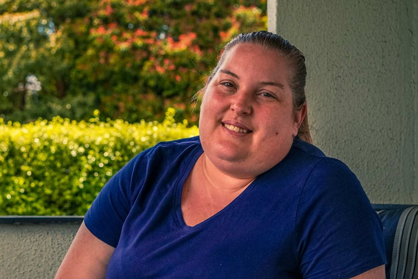 A woman in a blue t-shirt smiles for a photo on her porch, a green hedge behind her.