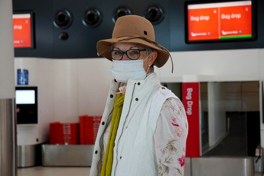 A woman wearing a brown hat, glasses and a face mask stands with a bag drop in the background.
