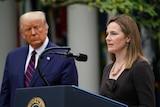Judge Amy Coney Barrett speaks at a podium next to US President Donald Trump