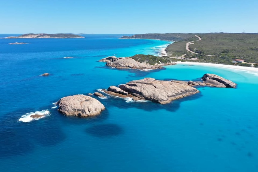 Twilight Beach is pictured by a drone, showing rocks, bright blue water, a road snaking along the coast