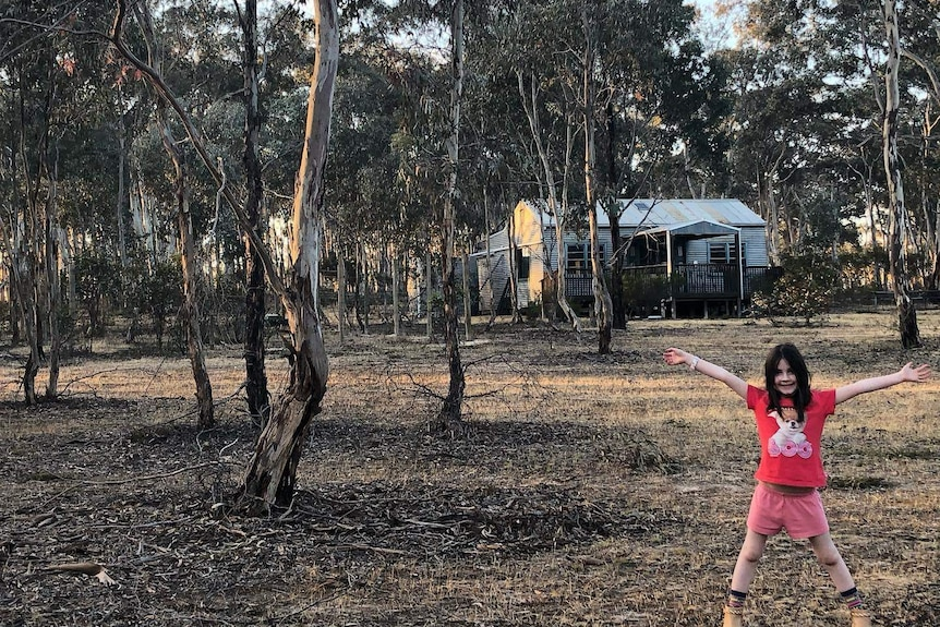 a young girl wearing a red t-shirt stands on a bush property with several gum trees and a rustic house