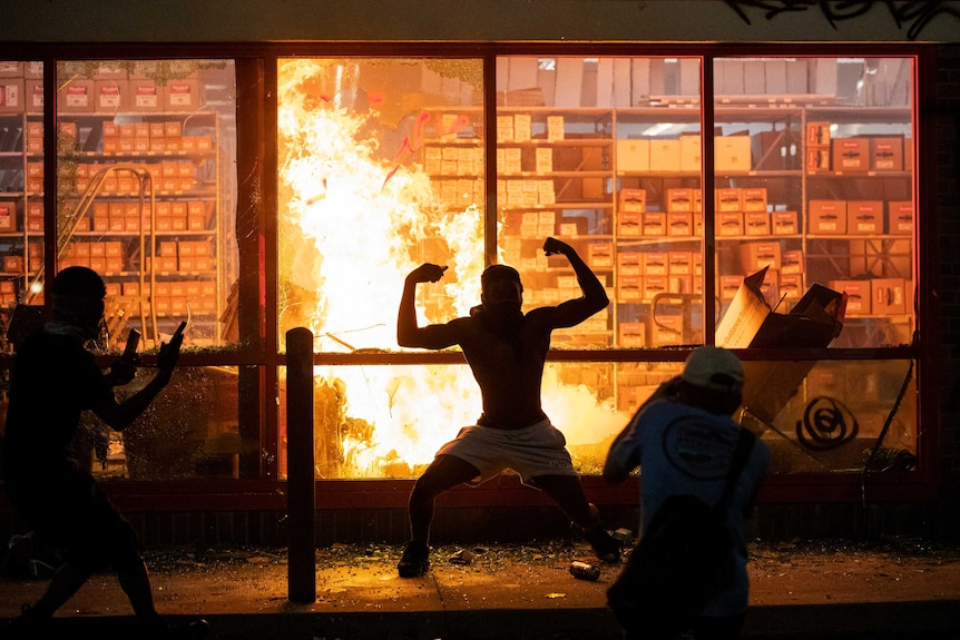 The silhouette of a man flexing both bicep muscles can be seen in front of a roaring fire inside a building.