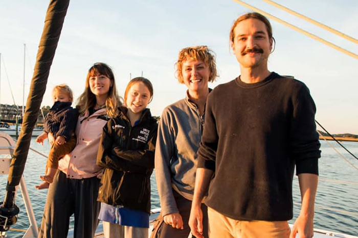 Four people stand on a yacht smiling.