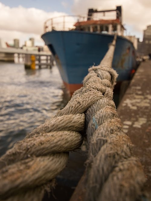 A close-up image of a rope tying a boat to a dock at port.