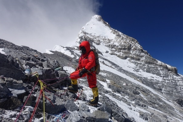 Man in red suit standing on a mountain with the summit of Everest behind him.