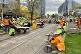 Construction workers wearing high-vis clothing blocking tram tracks.