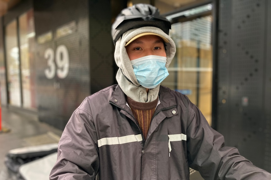 A person wears a rain jacket and helmet over a hood and a face mask on a grey day.