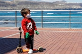 A child plays with a scooter at promenade of Las Canteras beach after restrictions were partially lifted.