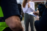 A police officer writes in a notebook as a young woman stands in the background