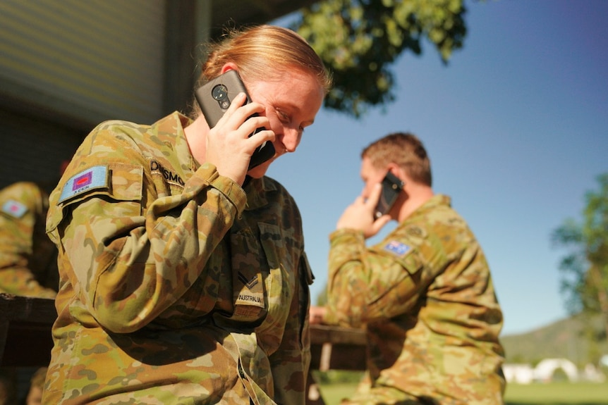 An army corporal sits on a seat outside in uniform, talking on the phone and smiling.