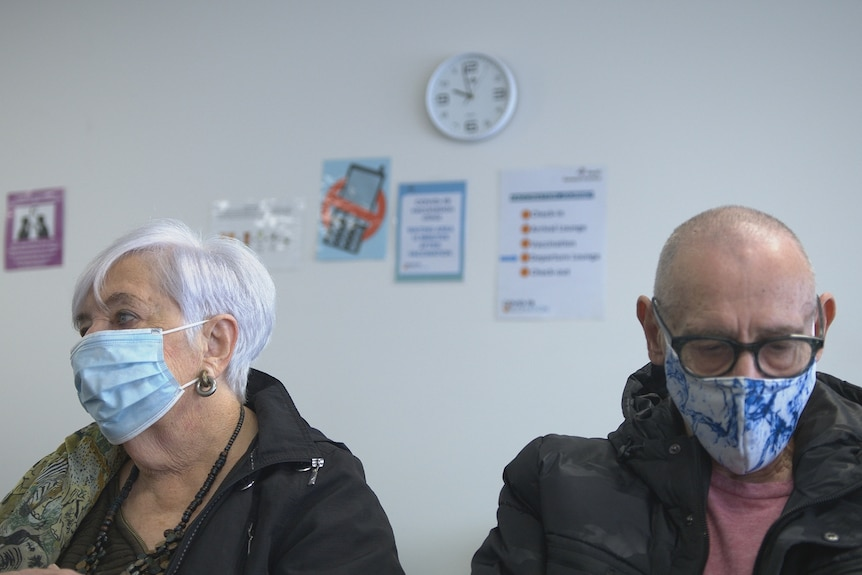 A woman and man wearing masks sit in the waiting room of a GP clinic. On the wall behind them is a clock.