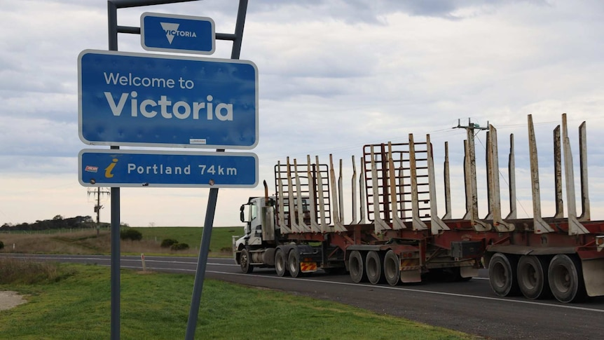 """A logging truck on the road next to a sign saying """"Welcome to Victoria, Portland 74km"""""""