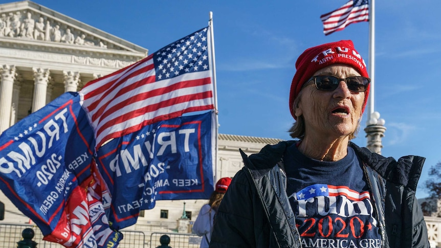 Activists demonstrate their support for President Donald Trump holding signs and US flags in front of the Supreme Court.
