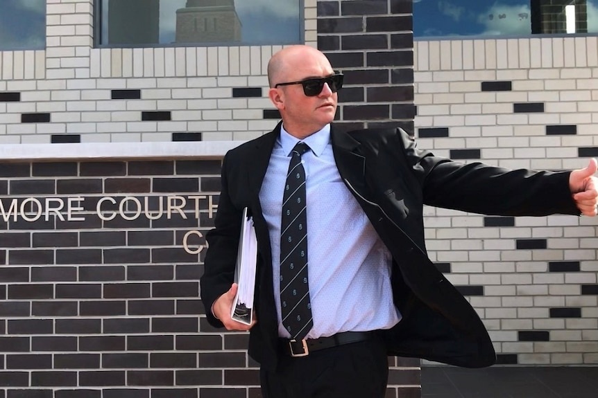 A bald man in a suit and dark sunglasses gestures with his hand as he walks past a court building.