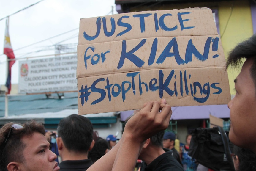 """A close up a protest sign reading """"Justice for Kian #stopthekilling""""."""