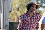 Indigenous actor Mark Coles Smith, wearing a hat and a checked shirt.